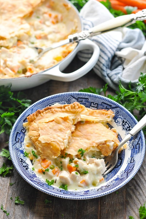 Front shot of easy chicken pot pie recipe in a blue and white serving bowl with a fork