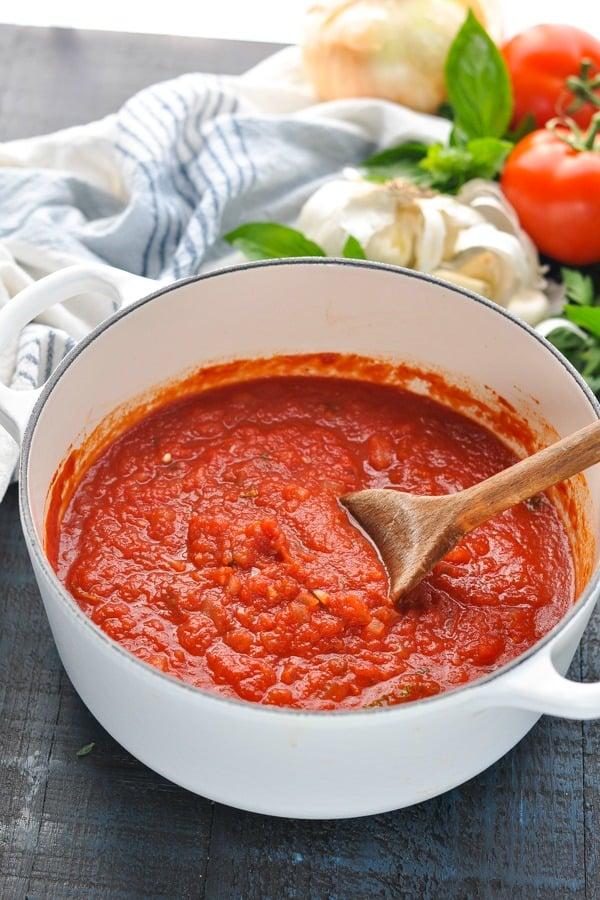 Homemade marinara sauce in a white cast iron pot