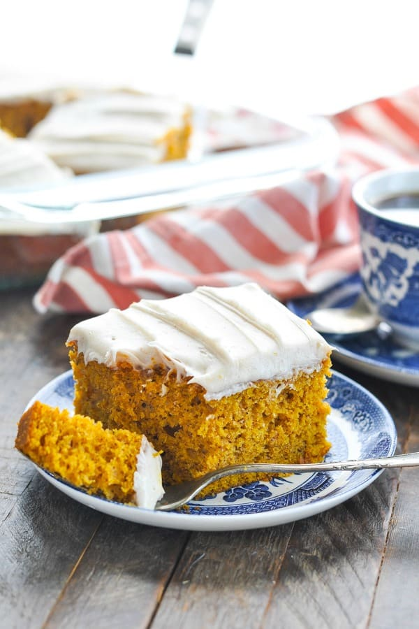 Side shot of a slice of pumpkin cake with cream cheese frosting on a blue and white plate