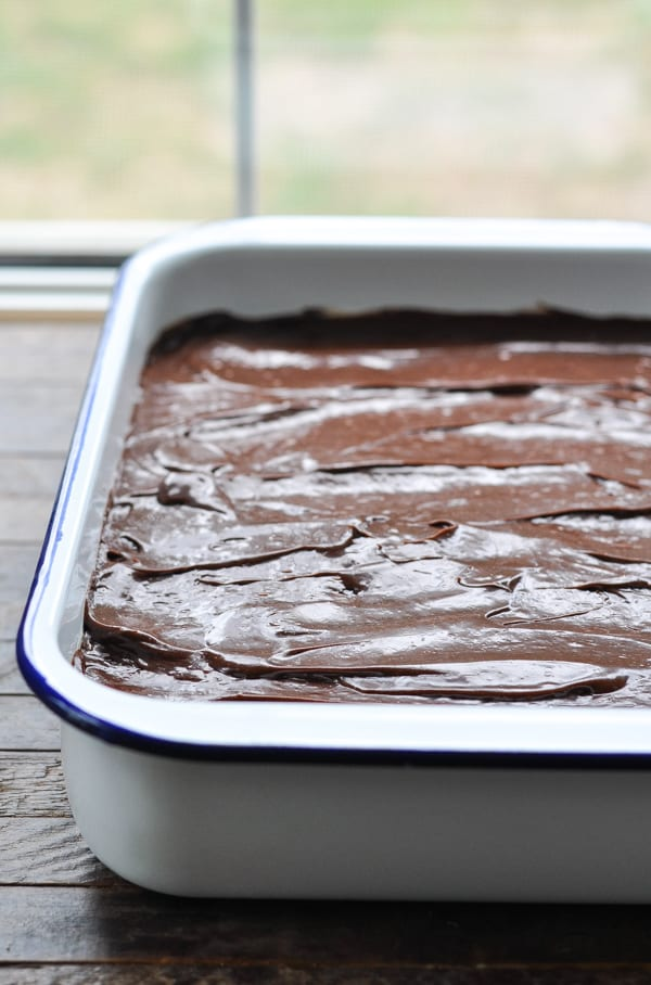 Spreading chocolate ganache on eclair cake