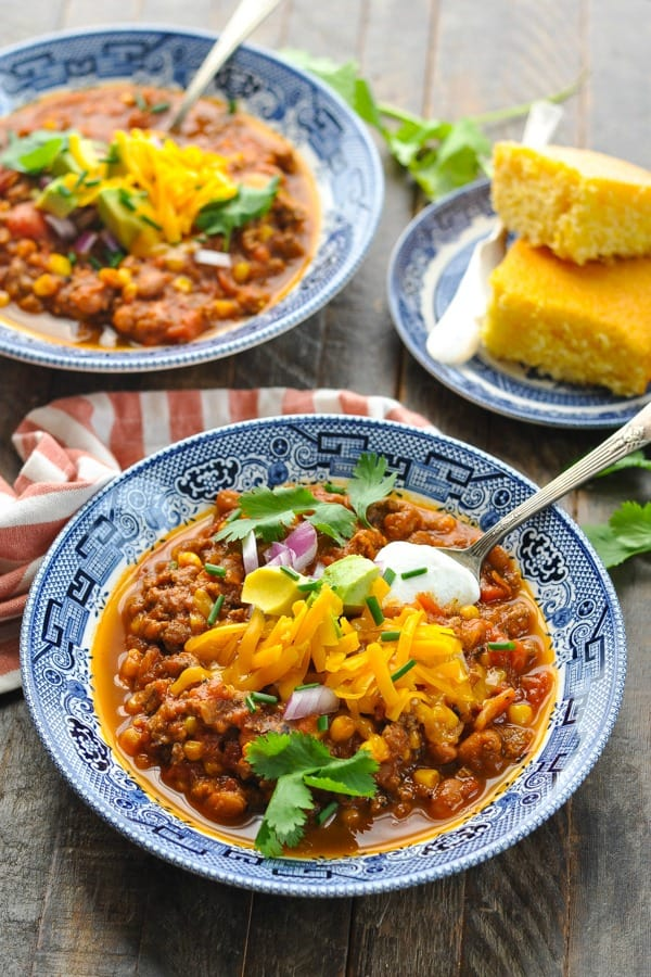 Front shot of two bowls of pumpkin chili served with cornbread