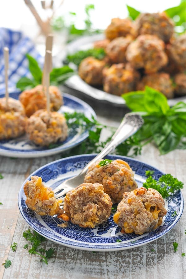 Front shot of sausage balls on a plate with fork cutting one in half