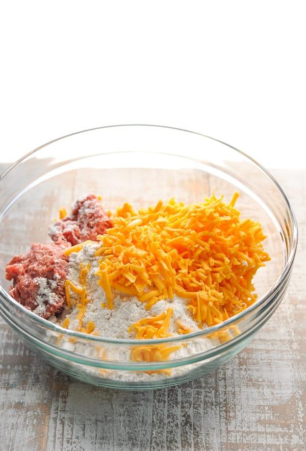Sausage ball ingredients in large glass mixing bowl