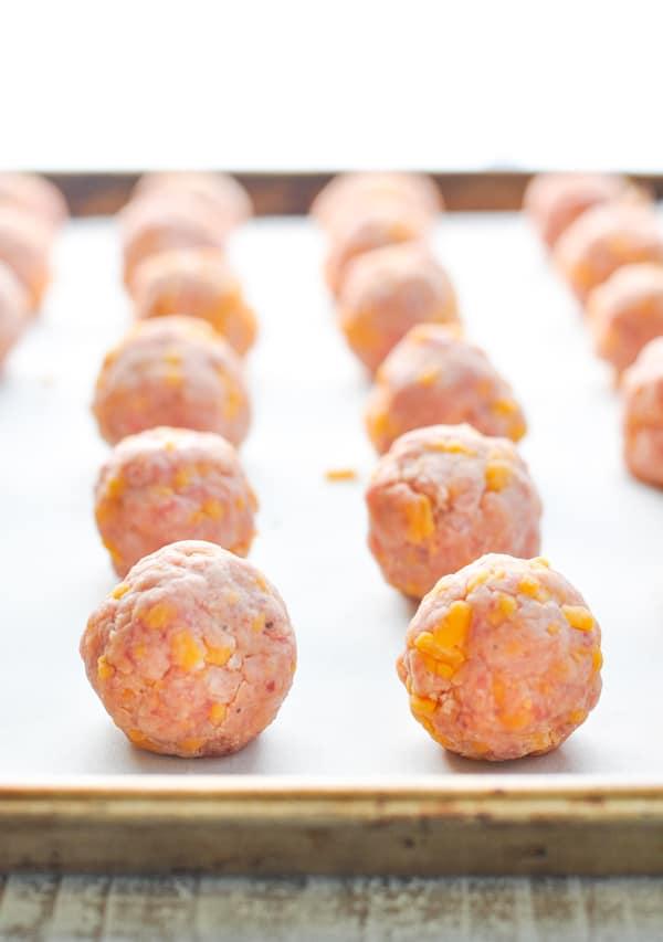 Raw sausage balls on baking sheet