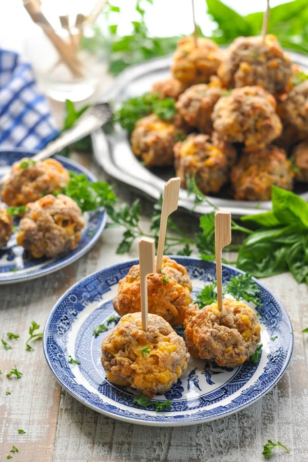 Sausage ball appetizers on plates surrounded by herbs