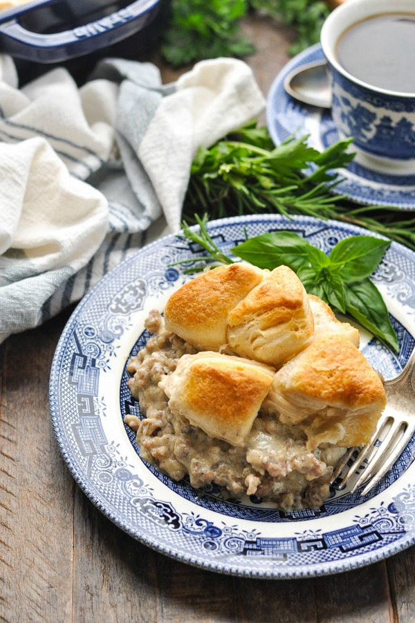 Serving of biscuits and gravy casserole on a blue and white plate with fresh herbs