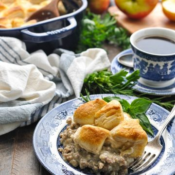Front shot of biscuits and gravy casserole on a wooden surface with fresh herbs and a cup of coffee