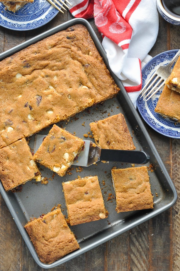 Close overhead shot of a pan of baked blonde brownies with white chocolate chips on a wooden table