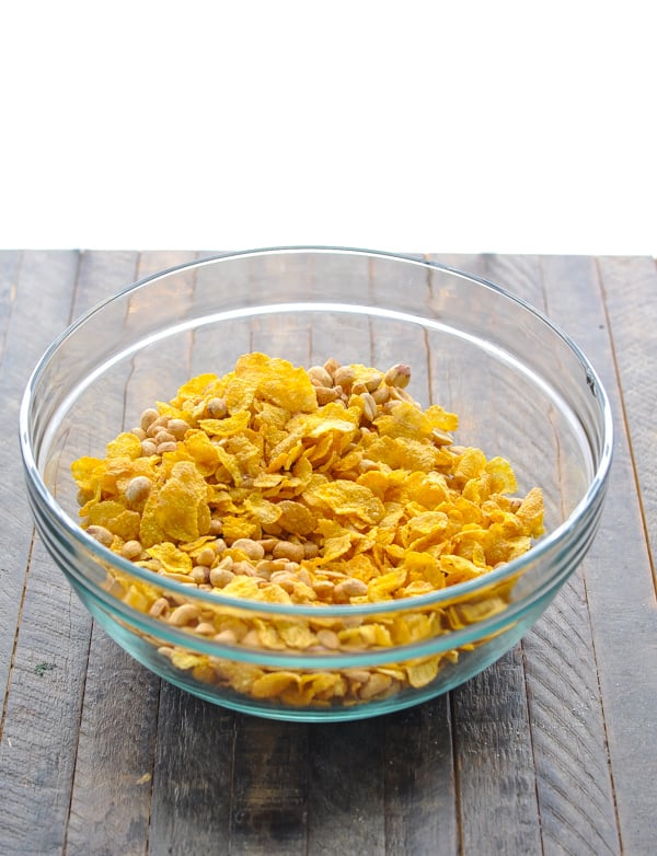 Peanuts and corn flakes cereal in a big glass mixing bowl