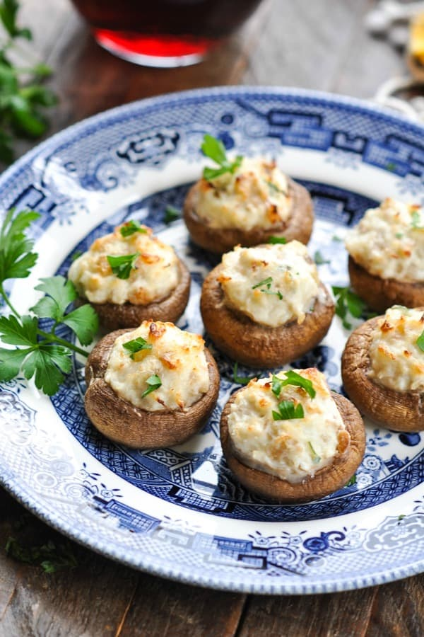 Blue and white plate of crab stuffed mushrooms garnished with fresh parsley