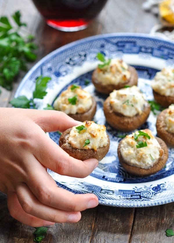 Fingers holding a crab stuffed mushroom garnished with parsley