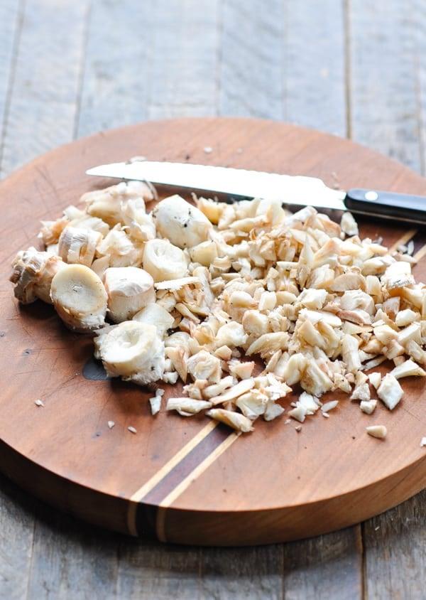 Chopped mushroom stems on a cutting board