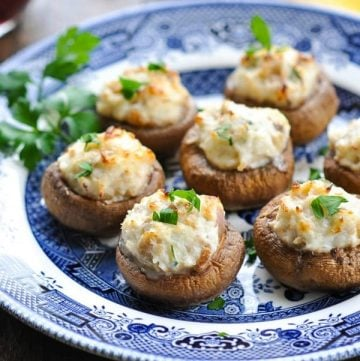 Close up front shot of crab stuffed mushrooms on a blue and white plate