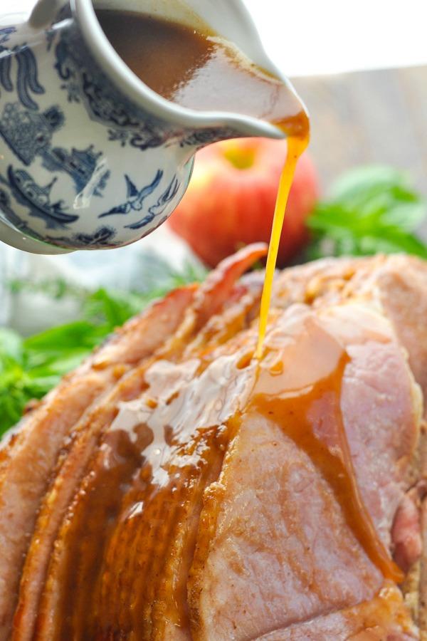 Pouring cola glaze over crock pot ham