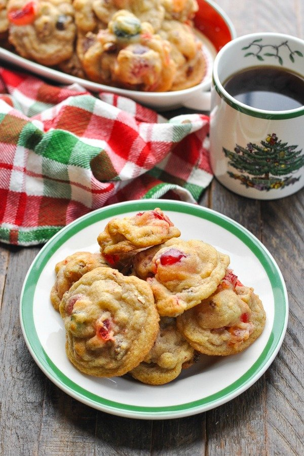 Above shot of fruitcake cookies on a plate with a mug of coffee in background