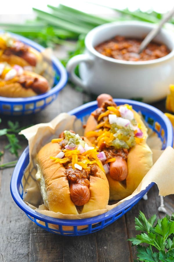 Close front shot of chili dogs in a basket with pot of hot dog chili in the background