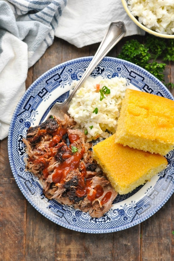 Close overhead shot of roasted pork shoulder on a blue and white plate with cornbread and coleslaw