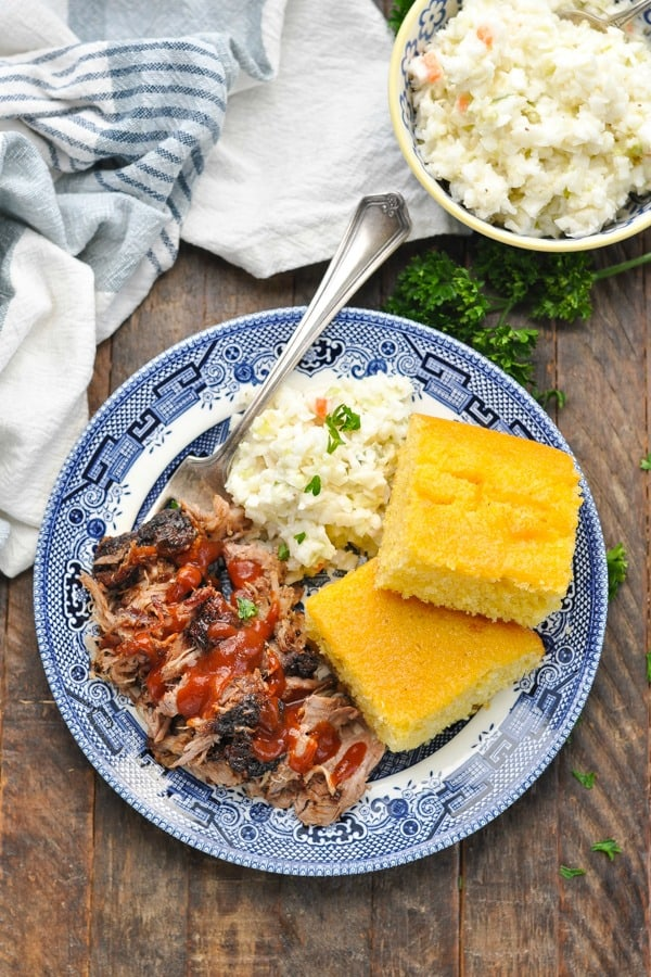Overhead shot of pulled pork on a plate with cornbread and coleslaw
