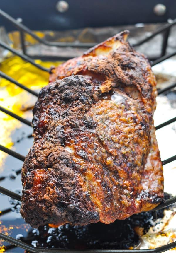 Crispy roasted pork shoulder on a rack in a roasting pan