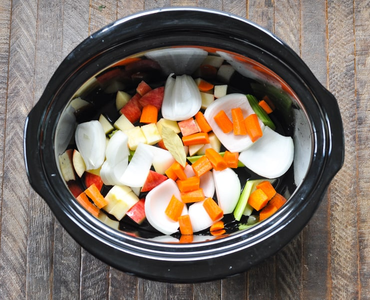 Vegetables chopped in bottom of slow cooker