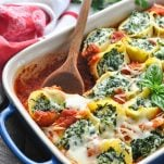 Close up image of spinach stuffed shells in a baking dish