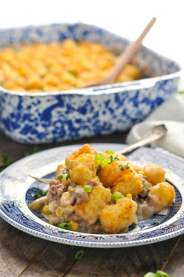 Close up front shot of cowboy casserole with ground beef tater tots and green beans on a blue and white plate