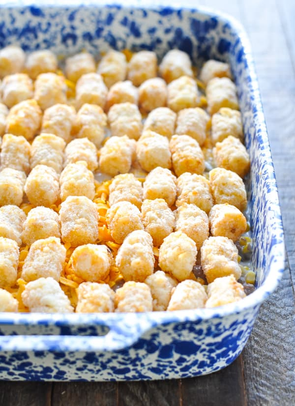 Frozen tater tots on top of cowboy casserole before baking