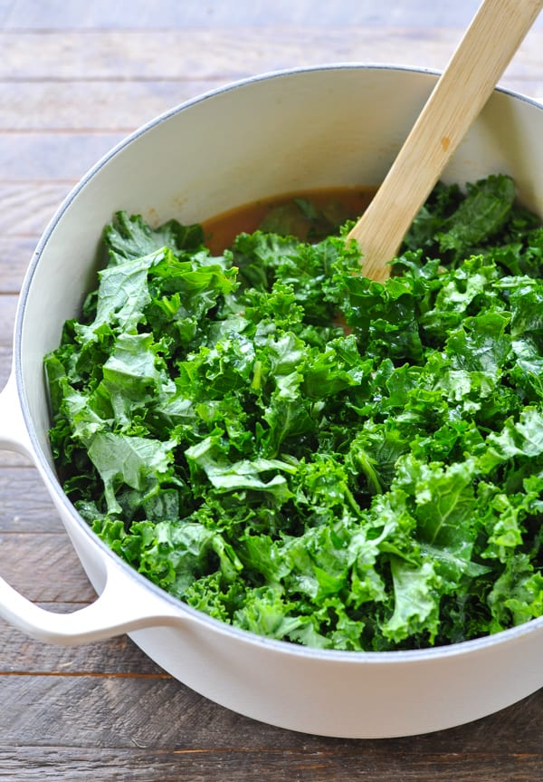 Fresh kale in a big white Dutch oven for white bean soup