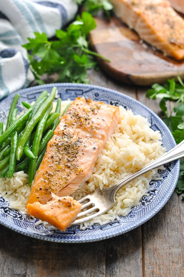 Baked salmon fillet on a plate with rice and green beans