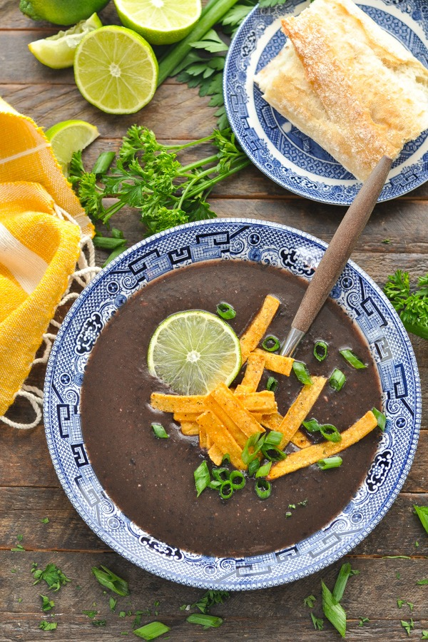 Close overhead shot of a bowl of healthy black bean soup recipe topped with tortilla strips and green onions and lime.