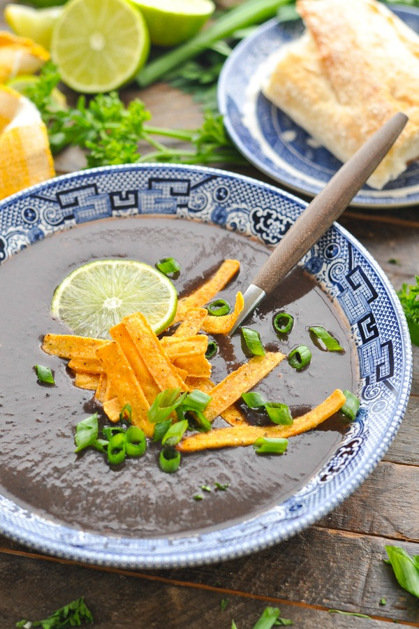 Close up front shot of black bean soup recipe in a blue and white bowl with toppings and sliced green onion on top