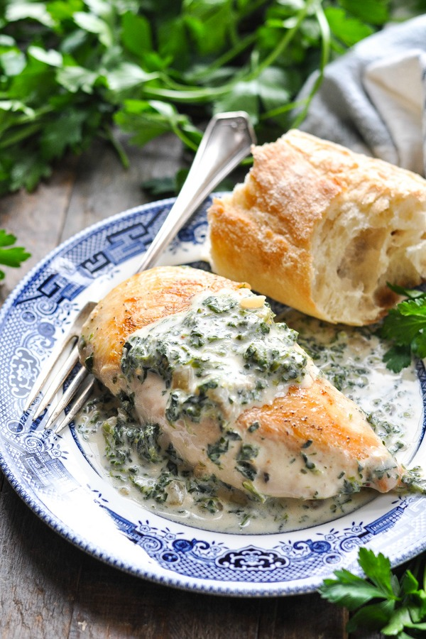 Close up front shot of chicken florentine on a blue and white plate with baguette