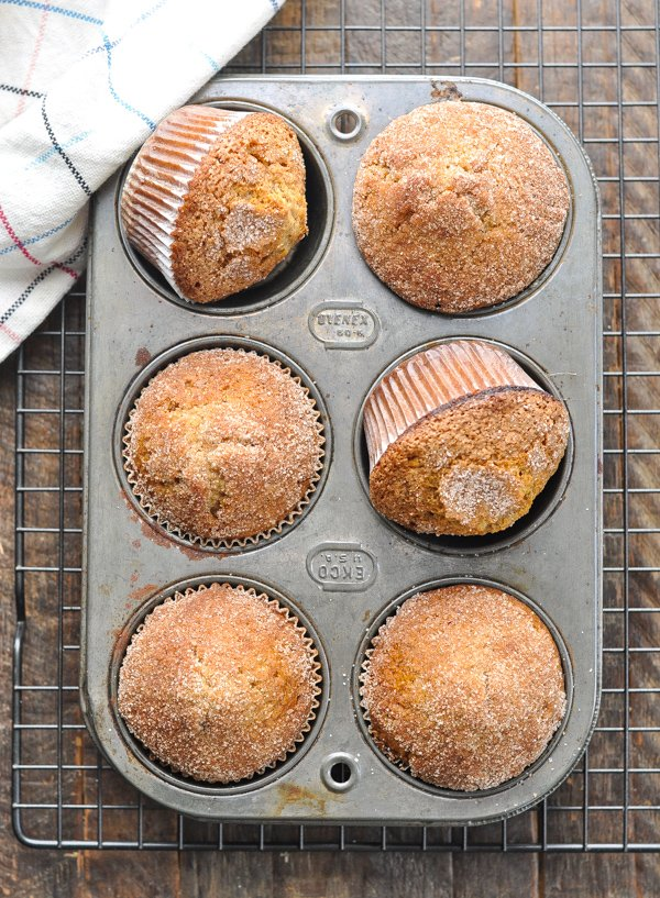 Overhead shot of cinnamon muffins in a muffin tin on a wooden surface