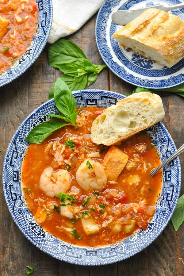 Overhead shot of cioppino recipe with fresh French baguette on the side