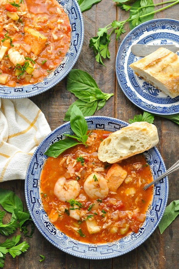 Overhead shot of slow cooker cioppino recipe served in two bowls with fresh herbs surrounding