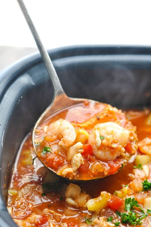 Serving of cioppino on a ladle in a slow cooker