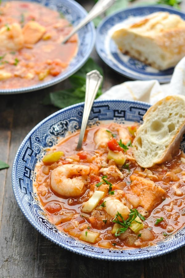 Close up front shot of a bowl of seafood cioppino with shrimp and crab on top