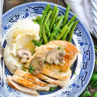 Overhead shot fo crock pot chicken and mushrooms recipe on a blue and white plate with mashed potatoes and green beans