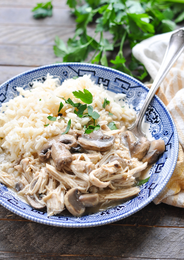 Close front shot of slow cooker chicken and mushrooms with mushroom gravy in a bowl with rice and fresh parsley