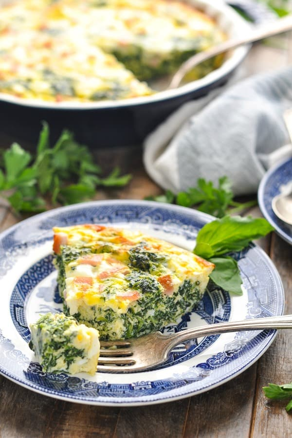 Front shot of a slice of crustless quiche with spinach with a bite taken out on a fork