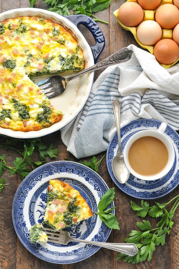 Long overhead shot of crustless quiche on a wooden table surrounded by herbs