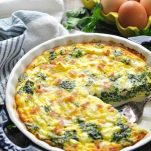 Front shot of a crustless quiche in a dish with a blue and white towel