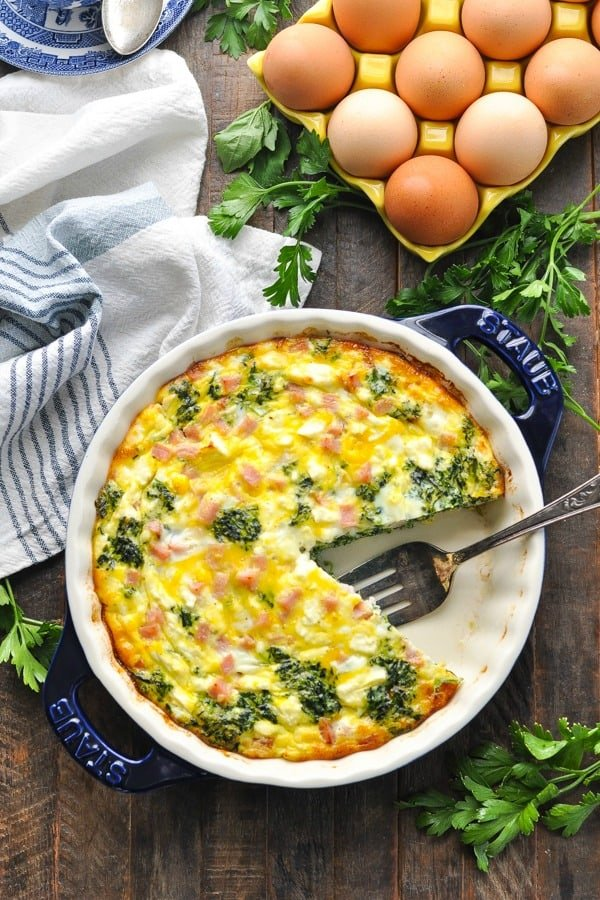 Long overhead shot of a crustless quiche with spinach in a blue pie plate