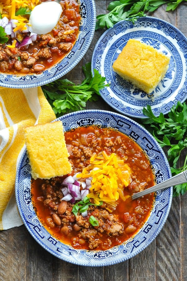 Overhead shot of a bowl of Instant Pot Turkey Chili with a side of cornbread