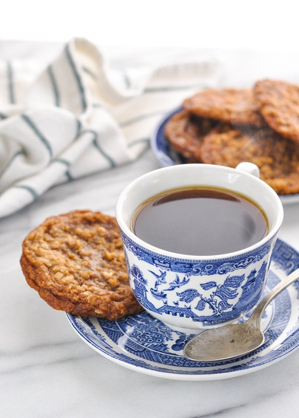 Cup of coffee with an oatmeal cream pie cookie on the saucer