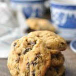 Close up shot of an oatmeal raisin cookie propped up against a stack of other cookies