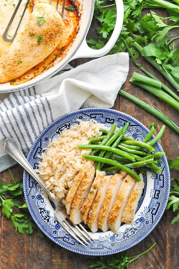 Overhead shot of parmesan crusted chicken breast on a plate with rice and green beans