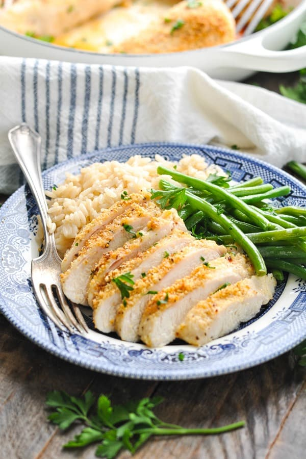 Close up front shot of sliced parmesan crusted chicken breast on a blue and white plate