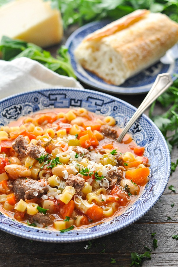 Bowl of pasta fagioli soup garnished with grated Parmesan and fresh herbs