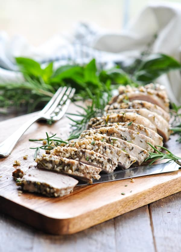 Crock Pot Pork Loin sliced on a cutting board